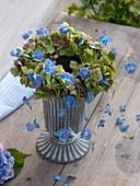 Kranz aus Hortensienblüten in Grün und Blau liegend auf Vase