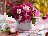 Strauß mit Rosen und Astern in kleiner Porzellantasse