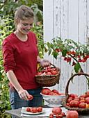Junge Frau hält Korb mit Tomaten