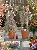 Herbstlicher Dekoration auf der Terrasse : Paar aus Heu gemacht in Tontöpfen