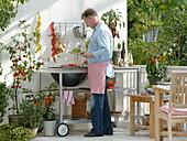 Outdoor - Küche auf dem Balkon : Mann grillt Paprika, Töpfe mit Glockenchili