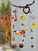Herbstliches Mobile aus Zweigen, Blättern, Früchten mit Windlichtern