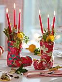 Kleine Nikolausstiefel gefüllt mit roten Stabkerzen, Orangenscheiben