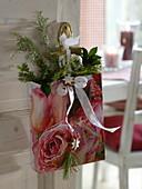 Aus Kalenderblatt gefaltete Papiertüte weihnachtlich dekoriert