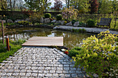 Teich mit Holzdeck und Acer palmatum 'Dissectum' (Japanischer Schlitzahorn),