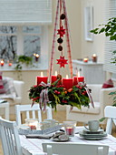 Gemischter Adventskranz mit roten Kerzen über dem Tisch aufgehängt
