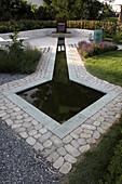 Wasserbecken mit Natursteineinfassung und Wasserspeier aus Stahl, Natursteinmauer