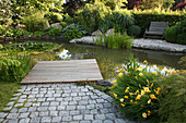 Teich mit Holzsteg und Bank : Nymphaea (Seerosen), Hemerocallis(Taglilien), Typha (Rohrkolben), Hosta (Funkien), Buxus (Buchs - Kugel), Holzbank am Kiesufer