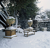 SNOW COVERED BENCH AND URNS IN THE Garden at CHISWICK HOUSE, London