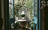 VIEW THROUGH BACK DOOR / French WINDOWS ONTO BRICK TERRACE of SMALL Town Garden with ARCHED TRELLIS & HEDERA On WALL & Box TREE IN Container DUSTED with SNOW. Designer: Anthony Noel