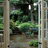 VIEW THROUGH French WINDOWS TO PAVED COURTYARD Dining AREA. STEPS FLANKED by LUSH FOLIAGE. Designer: JILL BILLINGTON