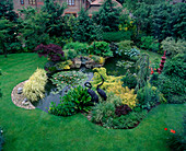 JAPANESE STYLE LILY POND AND WATERFALL SURROUNDED by EVER- GREENS & CONIFERS. HAM MANOR. Designer: Julian Treyer-Evans