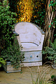 CORNER of Garden with CERAMIC CHAIR UNDER WICKER ARCH, with LIGHTING BEHIND. Designer: Emma LUSH