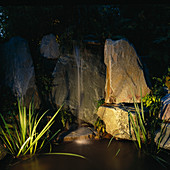 NIGHT-LIT Water Feature: Simple FOUNTAIN OVER ROCKS INTO POOL. LIGHTING by Garden & Security LIGHTING. NATURAL & ORIENTAL Water GARDENS, HAMPTON Court 97.