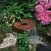 Water Feature: MILLSTONE WATERFALL SURROUNDED by FERNS, Rhododendron AND AQUILEGIA. DAILY MIRROR Garden, CHELSEA