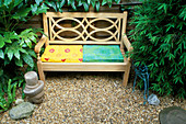 Tropical Garden with WOODEN BENCH AND BRIGHTLY COLOURED CUSHIONS, with Buddha'S HEAD, WIRE BIRD, FATSIA JAPONICA, ARUNDINARIA NITIDA, ASPLENIUM SCOLOPENDRIUM. Designer: ANDY REES