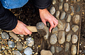 LOUISE GENTLY HAMMERS A PEBBLE INTO THE CEMENT Base