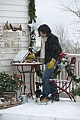 Winterbalkon mit Koniferen, Vogelfutterhaus, Schnee und Girlande