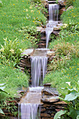 Water Feature: Water CASCADES THROUGH MEADOW with Primula PULVERULENTA AND Carex MORROWII IN THE WYEVALE / PORTMEIRION Garden, CHELSEA 99
