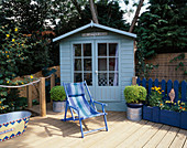 PAINTED BEACH Hut STYLE SHED STANDS Behind Blue STRIPED Canvas Deckchair, PAINTED TIN BATH AND RIBBED DECKING. ROBIN Green AND RALPH CADE'S SEASIDE STYLE Garden, LONDON.