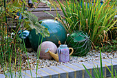 TURQUOISE CERAMIC BALLS, FISHING FLOATS AND A Spanish CERAMIC WATERING CAN STAND On GRAVEL. ROBIN Green AND RALPH CADE'S SEASIDE STYLE Garden, London