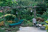 UNUSUAL Pergola Made From NATURAL TIMBER STANDS OVER Green Canvas Sun LOUNGER AND WOODEN Garden FURNITURE. BILL Smith AND DENNIS SCHRADERS Garden, Long Island, USA