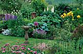 LAUNA SLATTER'S Garden, OXON: STONE BIRD TABLE AND BORDER with HOSTA 'Blue Moon', Yellow Iris, ACONITUM, LUPINS AND Viola CORNUTA
