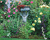 CAROLYN HUBBLE'S SHROPSHIRE GARDEN. Bronze Statue with English ROSE 'REDOUTE', Rosa 'Magenta' AND Rosa 'Charlotte'