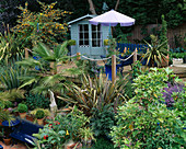 SLOPING BACK Garden with UPPER DECK of DECKING with Rope EDGING, Blue SUMMERHOUSE, PHORMIUM, TRACHYCARPUS FORTUNEI AND PARASOL. ROBIN Green & RALPH CADE'S Garden, London