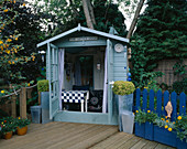 THE 'UPPER DECK' with Blue WOODEN SUMMERHOUSE AND DECKING. ROBIN Green & RALPH CADE'S Garden, London