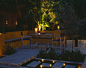 A PLACE TO SIT: Aluminium TABLE AND CHAIRS On Patio SURROUNDED by Yellow RENDERED WALLS with RAISED BEDS AND RILL. .EVENING LIGHTING with CANDLES AND LANTERNS. Designer Joe SWIFT
