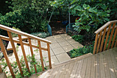 VIEW ONTO CHILDRENS Garden From DECKED TERRACE: SWINGS with BARK BENEATH, Blue TRELLIS SCREENS, PAVING, WOODEN SEAT, FIG. Designer: Sarah LAYTON
