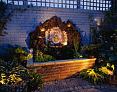 Water Feature: RECTANGULAR BRICK Pool with SHELL WALL FOUNTAIN BACKED by Rock AND BRICK WALL PAINTED Blue, LIT UP at NIGHT. Designer: ANDREW ANDERSON