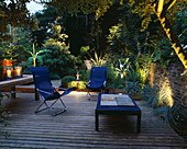 DECKED TERRACE with LIGHTING: Blue DECK CHAIRS, Blue TABLE, WOODEN TABLE with CANDLES, BAMBOO (MUSA BASJOO) AND AGAVE. LIGHTING by Garden & Security LIGHTING