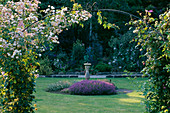 EASTLEACH HOUSE Garden, Gloucestershire: SUNDIAL, PINKS, THYME AND ROSE ARCH of 'PRINCESS LOUISE'
