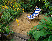 SANDPIT with RAILWAY SLEEPER EDGES AND DECKCHAIR. DAVID AND MARIE CHASE'S Garden, Hampshire