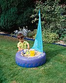JOSHUA PLAYS IN THE TYRE SANDPIT On THE LAWN. THE SAIL IS Made of Kite Material