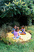 JASMINE, ANDY AND SHANA HICKS SIT On THE Yellow Circle of DECK SURROUNDED by RHUS typhina, BIDENS AUREA, HELICHRYSUM, STIPA TENUISSIMA AND Carex BUCHANANII: DESIGN: Clare MATTHEWS