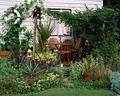SEASIDE STYLE Garden with WOODEN SLEEPERS, WOODEN TABLE AND CHAIRS AND Cream COLOURED CANOPYIN DAVID AND MARIE CHASE'S Garden, Hampshire