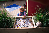 CHILDRENS DECK Garden: Lucy FEELING THE SHELLS, FIR CONES AND STONES IN A RAISED WOODEN BED