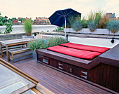 ROOF Garden DESIGNED by STEPHEN WOODHAMS: DECKED TERRACE with GALVANISED CONTAINERS with FESTUCA GLAUCA, STIPA ARUNDINACEA, STIPA TENUIFOLIA. Canvas UMBRELLA / Sun LOUNGER