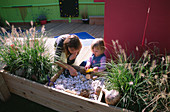 CHILDRENS DECK Garden: Lucy AND Clare FEELING THE SHELLS, FIR CONES AND STONES IN A RAISED WOODEN BED: Designer: Clare MATTHEWS