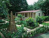 FAMILY POTAGER by Clare MATTHEWS: GRAVEL, WOODEN OBELISKS, CLIPPED Box AND Bay AND A SUMMERHOUSE