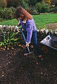 Clare MATTHEWS MIXING COMPOST INTO THE SOIL IN HER Garden IN Devon