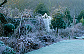 West Green HOUSE Garden, Hampshire: FROSTY BORDER IN Winter with SEDUMS AND WOODEN TRIPODS IN Front of A White Ornamental SEAT IN THE WALLED Garden