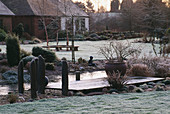 WOODEN LANDING STAGE with Container IN Frost Beside THE Pool with THE HOUSE IN THE BACKGROUND JOHN MASSEYS Garden, WORCESTERSHIRE