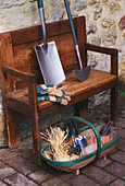 WOODEN BENCH Beside WALL with TRUG, GLOVES AND Spade