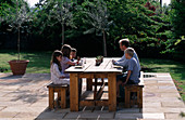 Designer Clare MATTHEWS: STONE TERRACE with TABLE AND CHAIRS AND FAMILY ENJOYING Breakfast
