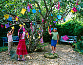 Designer Clare MATTHEWS: CHILDRENS Party - GIRLS with SELF Made Party HATS HANGING FLOWER MOBILES ONTO an Apple TREE IN THE GRAVEL Garden