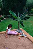 Designer: Clare MATTHEWS - Tropical Island SANDPIT - WOODEN FRAMEWORK with CROSS FRAME AND PLASTIC SHEETING, Banana, PEBBLES, Sand, Girl AND Boy